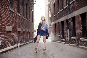 Caucasian woman standing in city alleyway