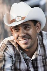 Hispanic man smiling in cowboy hat