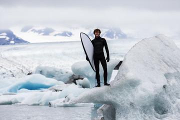 Caucasian surfer carrying board near glacial water