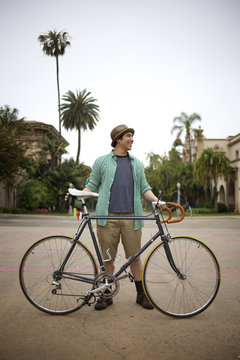 Pacific Islander man standing with bicycle