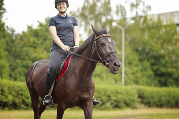 Girl riding a horse. Girl in dark helmet, jeans and high boots on a brown horse