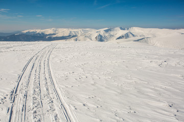 skiing tracks at a summit of high mountain range