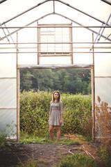 Woman standing in greenhouse doorway