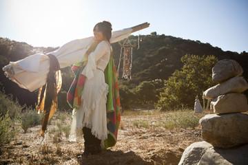 Hispanic woman carrying teepee in desert