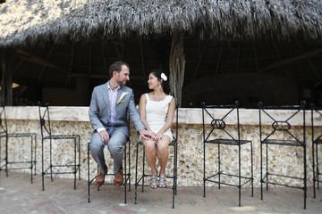 Newlywed couple sitting on bar stools
