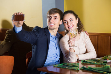 young cute couple photographing yourself on your smartphone for