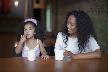 Mixed race mother and daughter drinking hot chocolate