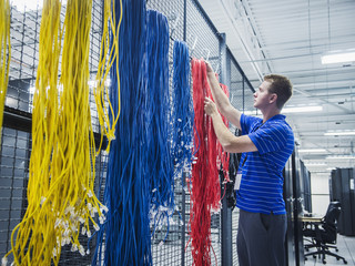 Caucasian technician hanging cables in server room