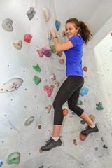 junge Frau hat Spass beim Bouldern