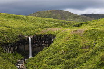 Waterfall in rolling hills in remote landscape