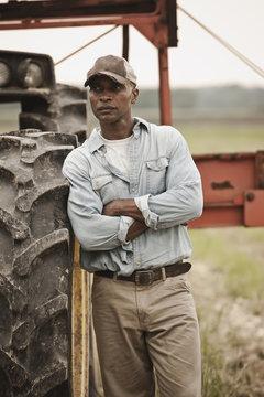 African American farmer standing near tractor