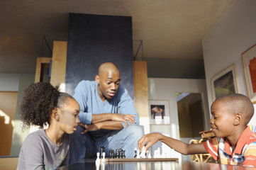 Black father watching children play chess