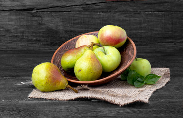 apple and pear on the plate - summer fruit on wooden background