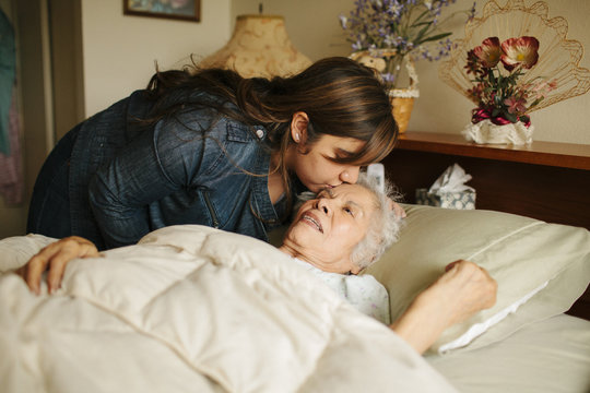 Granddaughter kissing forehead of grandmother in bed