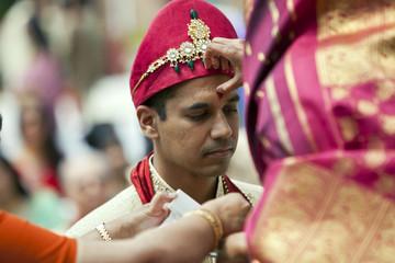 Indian woman marking groom's forehead
