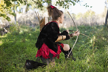 Caucasian girl in costume holding bow and arrow
