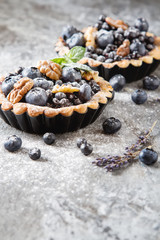 Homemade blueberry pie with mint and lavender. gray stone table
