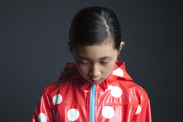 Sad Asian girl wearing raincoat