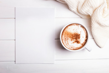 Cappucino, sweater and blank paper