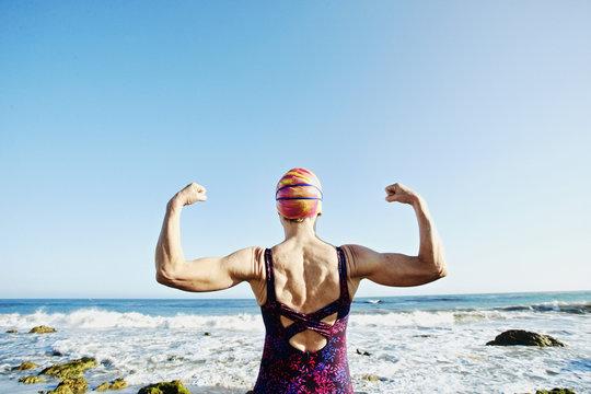 Senior woman flexing her muscles on beach
