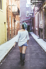 Caucasian woman walking in urban alleyway