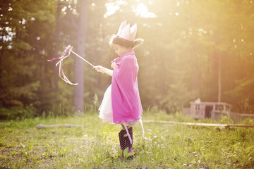 Girl playing princess in backyard
