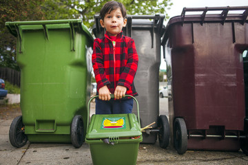Mixed race boy carrying compost bin outdoors