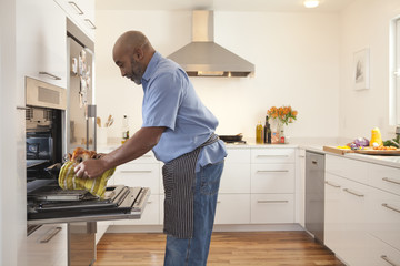 African American man taking food out of oven