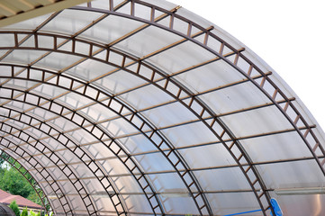 A canopy made of polycarbonate arc against the blue sky. Metal construction.