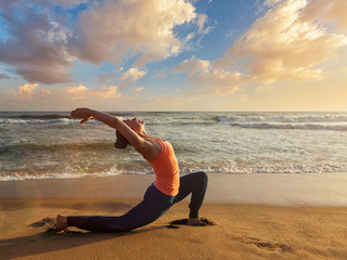 Sporty fit woman practices yoga Anjaneyasana at beach on sunset