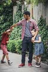 Mixed race brothers and sister playing on suburban sidewalk