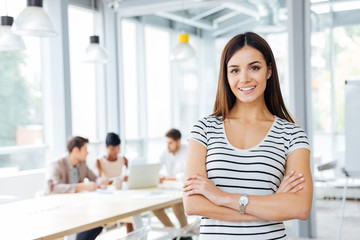 Happy woman standing with arms crossed in office