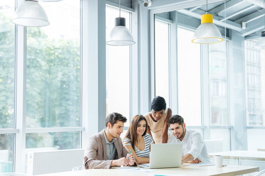 Business people creating presentation and using laptop together in office
