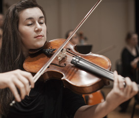 Caucasian woman playing violin in orchestra