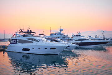 Extra Large Luxury yachts rest in the port at sunset Wall mural