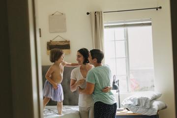 Caucasian family hugging in bedroom