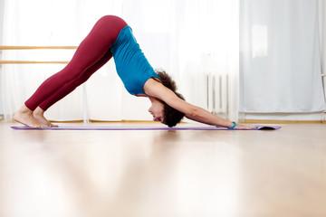 Full length portrait of woman doing sun salutation yoga complex