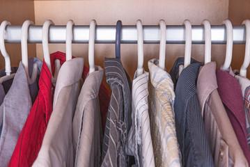 Selection of men's shirts hanging inside a wardrobe