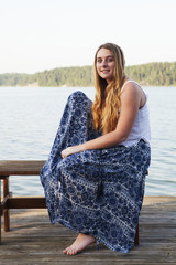 Caucasian teenage girl sitting on wooden dock at lake