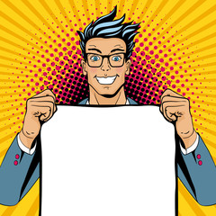 Wow pop art man. Young happy surprised man in glasses with open smile holding empty poster. Vector illustration in retro comic style. Vector pop art background.
