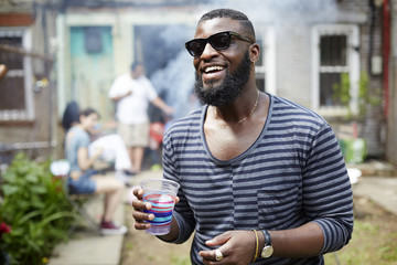 African American man drinking at backyard barbecue