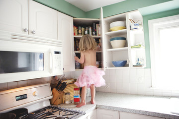 Semi-nude girl looking in cupboard on kitchen counter