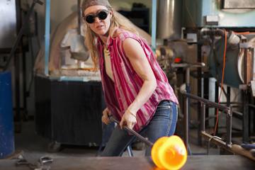 Caucasian woman in glass blowing studio