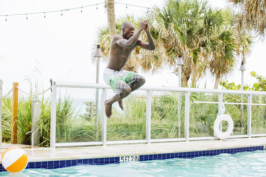 Black man jumping into swimming pool