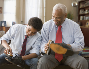 Black grandson and grandfather shining their shoes