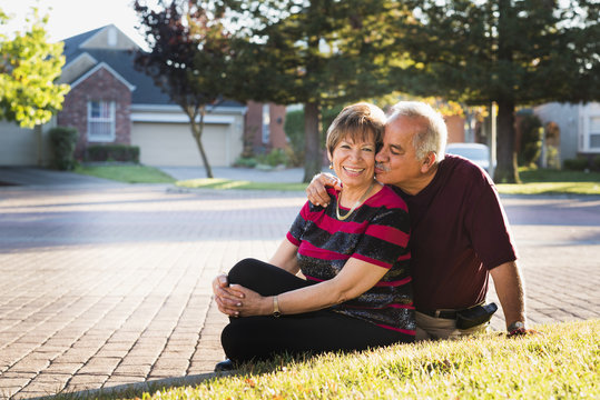Older Hispanic couple kissing outside suburban home