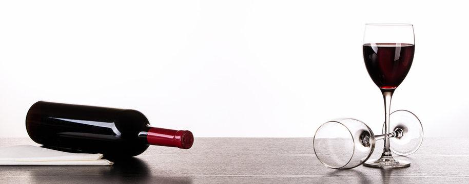 Rotweinflasche und Weingläser auf schwarzem Holztisch vor weißem Hintergrund. Makro, Panorama