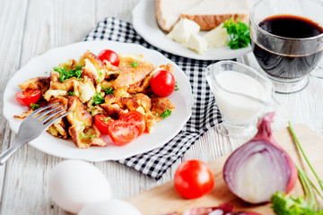 Traditional hearty breakfast , egg omelette with herbs , tomato , onion , toast, butter , cream and black coffee on a wooden background