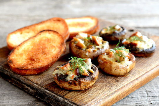 Delicious mushroom caps stuffed with cheese and meat and baked in the oven. Fried toasts of white bread. Wooden background