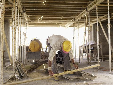 Hispanic worker measuring lumber at construction site
